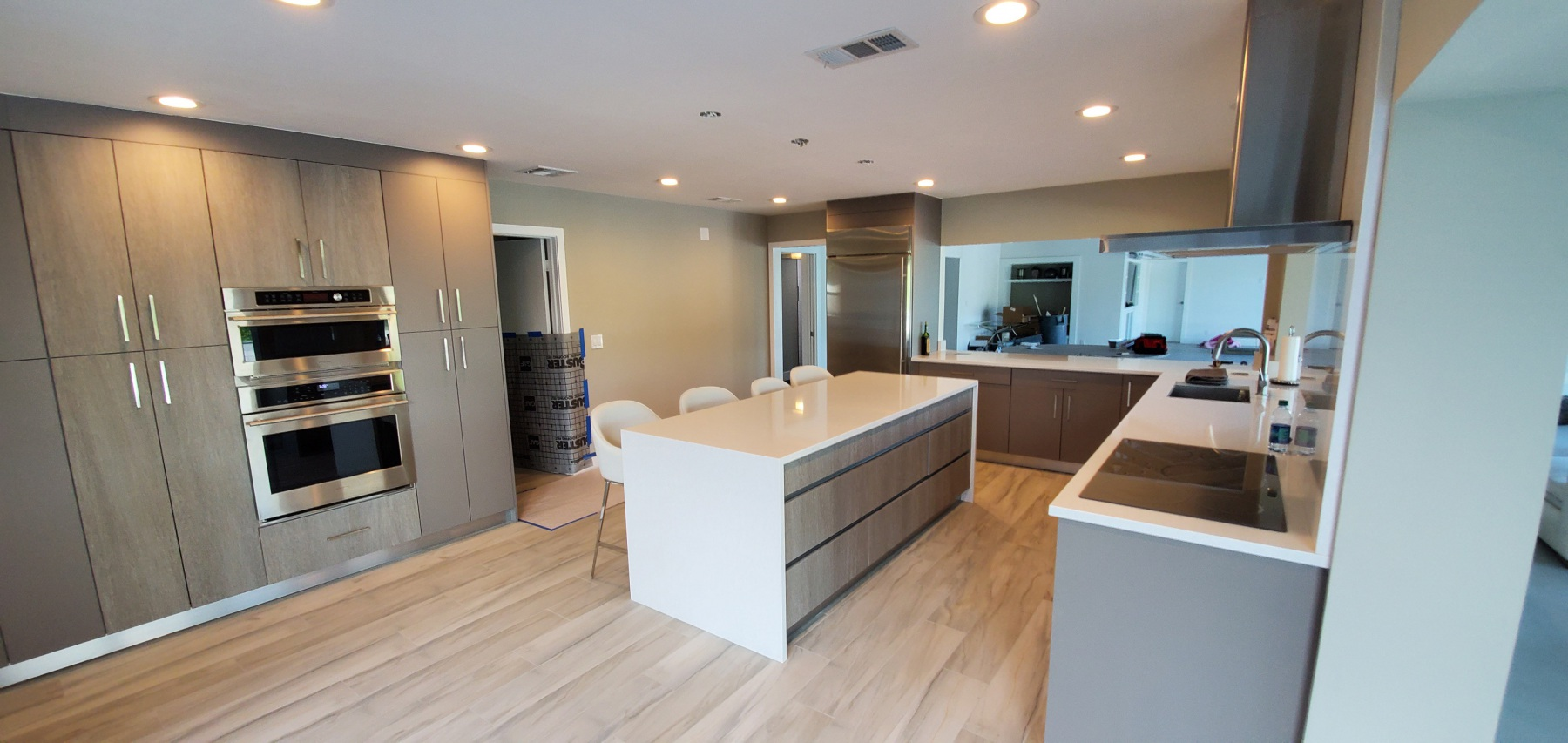 Remodeled Kitchen in Boca Raton with Modern cabinets, waterfall island, and built in double oven