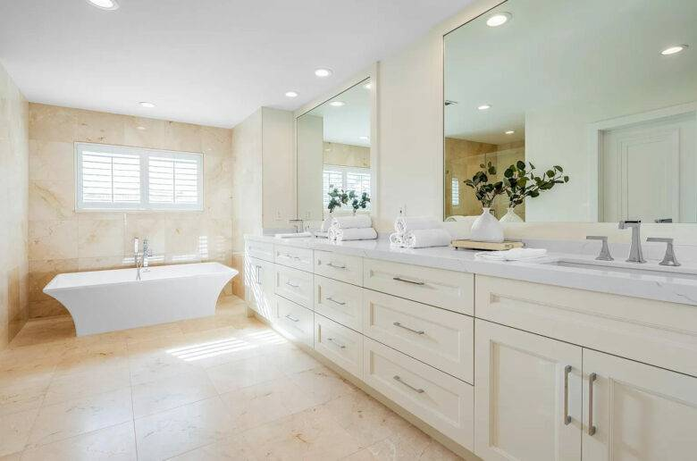 Bath Remodel in Boca Raton with his and hers double vanity, mirrors, and modern bathtub